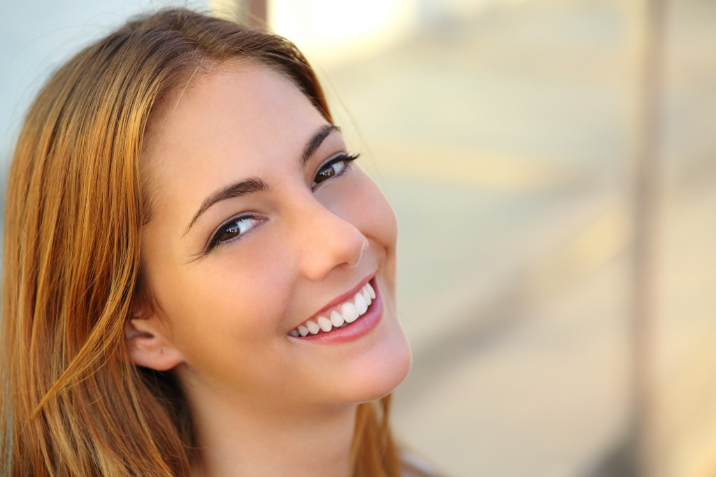 Beautiful woman with a perfect white smile and smooth skin with an unfocused background