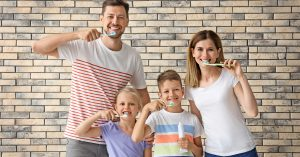 a family practices dentistry together by brushing their teeth