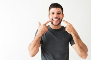 A man points to his restorative dentistry solutions.