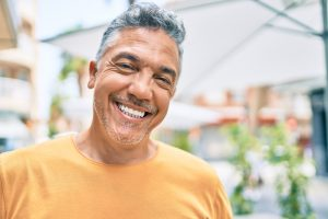 A man smiles confidently following his teeth whitening treatment.